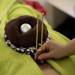 Klangei mit Klangnest und Stimmgabel während einer Massageanwendung