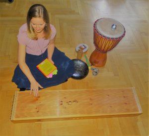 Frau mit Musikinstrumenten aus Holz