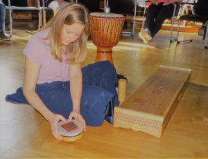 Frau im Kleid sitzt auf dem Boden mit Instrumenten